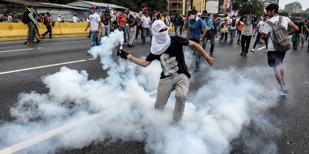 TOPSHOT - Demonstrators clash with the riot police during a protest against Venezuelan President Nicolas Maduro, in Caracas on April 20, 2017.Venezuelan riot police fired tear gas Thursday at groups of protesters seeking to oust President Nicolas Maduro, who have vowed new mass marches after a day of deadly unrest. Police in western Caracas broke up scores of opposition protesters trying to join a larger march, though there was no immediate repeat of Wednesday's violent clashes, which left three