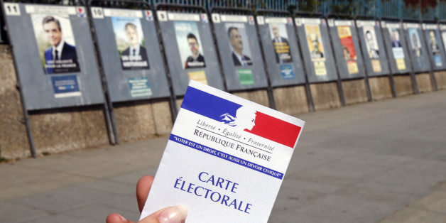 PARIS, FRANCE - APRIL 20:  In this photo illustration, a French voter registration card is seen in front of official campaign posters for all eleven candidates for the 2017 French presidential elections posted outside a polling station on April 20, 2017 in Paris, France. French 2017 presidential election which will take place on April 23 and May 07, 2017.  (Photo Illustration by Chesnot/Getty Images)