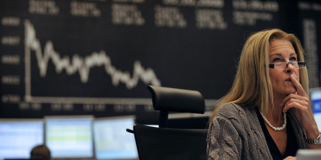 A share trader checks share prices as she sits behind her trading terminals at the trading floor of the German stock exchange in Frankfurt, October 20, 2008.   REUTERS/Kai Pfaffenbach(GERMANY)