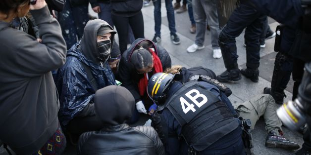 French anti-riot police forces tend to a demonstrator lying on the ground in Paris on April 23, 2017 following the announcement of the results of the first round of the Presidential election.Centrist Emmanuel Macron finished ahead of far-right leader Marine Le Pen on Sunday to qualify alongside her for the runoff in France's presidential election, initial projections suggested.  / AFP PHOTO / Benjamin CREMEL        (Photo credit should read BENJAMIN CREMEL/AFP/Getty Images