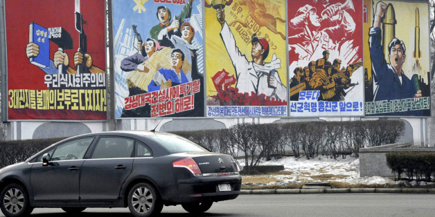 A car passes propaganda billboards hailing economic projects and the military along a roadway in Pyongyang December 21, 2010. REUTERS/Kyodo (NORTH KOREA - Tags: SOCIETY POLITICS) JAPAN OUT. NO COMMERCIAL OR EDITORIAL SALES IN JAPAN. FOR EDITORIAL USE ONLY. NOT FOR SALE FOR MARKETING OR ADVERTISING CAMPAIGNS. THIS IMAGE HAS BEEN SUPPLIED BY A THIRD PARTY. IT IS DISTRIBUTED, EXACTLY AS RECEIVED BY REUTERS, AS A SERVICE TO CLIENTS