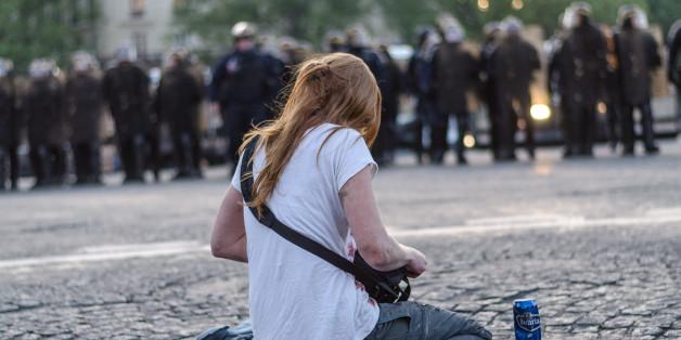 Junge Frau sitzt nach dem ersten Wahlgang zur Präsidentschaftswahl in Paris Polizisten gegenüber
