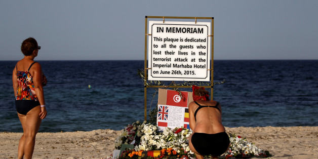 Tourists pay their respects at a plaque dedicated to victims on the beach of the Imperial Marhaba resort, on the first anniversary of an attack by a gunman at the hotel in Sousse, Tunisia June 26, 2016.  REUTERS/Zohra Bensemra