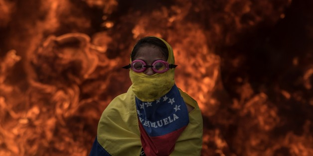 CARACAS, VENEZUELA - APRIL 24: Venezuelan opposition activist cover his face in front of burning barricades as the protesters block a main highway during a march against the government of President NIcolas Maduro, in Caracas, on April 24, 2017. Venezuela is grappling with a new wave of political protest since April 4 that has led to the deaths of 21 people. (Photo by Carlos Becerra/Anadolu Agency/Getty Images)