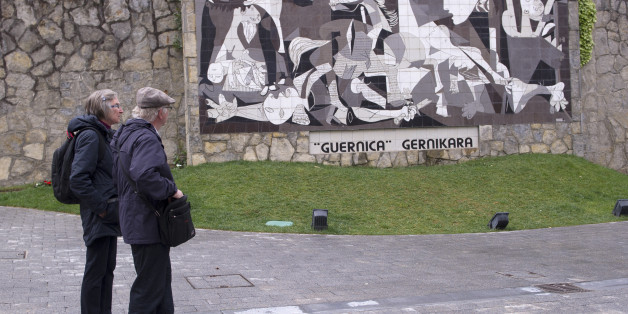 A couple watch a mural depicting Picasso's painting 'Guernica' in the Spanish northern Basque village of Gernika on April 26, 2017.Guernica commemorates today the 80th aniversary of the bombing raid of the small Basque town of Guernica by Nazi aircraft, at the behest of General Francisco Franco on 1937. / AFP PHOTO / ANDER GILLENEA        (Photo credit should read ANDER GILLENEA/AFP/Getty Images)
