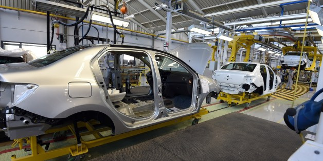 Employees of the French car maker Renault group work on a new production line during its inauguration on November 10, 2014, in Oued Tlelat in the south of the Algerian city of Oran. The factory is to produce the Symbol, a saloon based on Renault's Clio compact sold mainly in markets where hatchbacks are not traditionally favoured. Production is destined for the Algerian market, Africa's second largest in terms of sales, with more than 400,000 vehicles imported every year. AFP PHOTO / FAROUK BATI