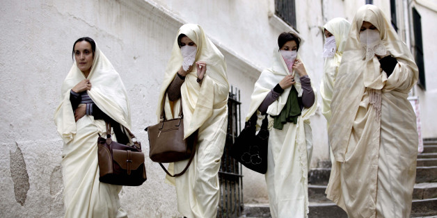 Group of women wearing haiks, long white embroidered gowns, Algerian women's traditional dress, walking in a lane of Algiers kasbah. (2015/11/21). (Photo by: Andia/UIG via Getty Images)