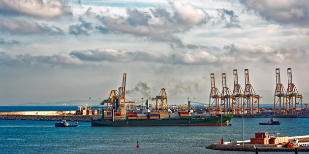 Containership arriving port Valencia with the assistance of two harbour tugs. Spain, Europe