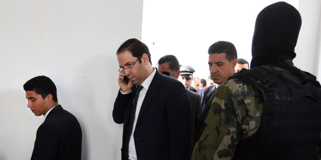 Tunisian Prime Minister Youssef Chahed talks on the phone upon his arrival in the town of Tataouine on April 27, 2017. 