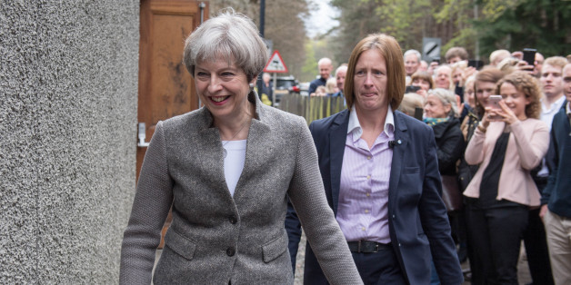 Britain's Prime Minister Theresa May (C) goes door-to-door campaigning for Andrew Bowie, Conservative candidate for West Aberdeenshire and Kincardine in the village of Banchory, in Aberdeenshire, north east of Scotland, on April 29, 2017 during a general election campaign visit.  Britain goes to the polls to elect a new parliament in a general election on June 8. / AFP PHOTO / Michal Wachucik        (Photo credit should read MICHAL WACHUCIK/AFP/Getty Images)