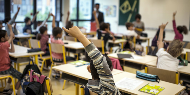 Pupils raise their hands in a classroom at the Germaine Tillion primary school, on September 4, 2012 at the start of the new school year in Lyon, eastern France. Tillion (1907-2008) was a French anthropologist, specialist of Algeria and resistant fighter during World War II.   AFP PHOTO /        (Photo credit should read JEFF PACHOUD/AFP/GettyImages)