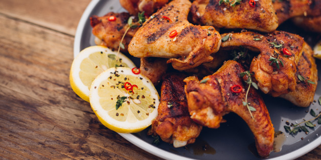 Spicy chicken wings sprinkled with chillie and herbs on a vintage wooden table