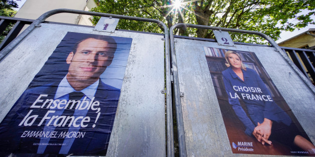 New official posters for the candidates for the 2017 French presidential election, Emmanuel Macron (L), head of the political movement En Marche !, or Onwards !, and Marine Le Pen (R), French National Front (FN) political party leader, are displayed in Caluire, near Lyon, France, April 30, 2017. REUTERS/Robert Pratta