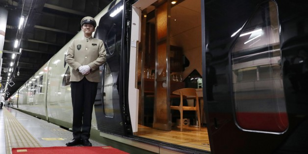 This picture taken on April 26, 2017 shows a crew member standing next to the Train Suite Shiki-Shima, operated by East Japan Railway, at Ueno Station in Tokyo during a press preview.The luxury sleeper Shiki-Shima, which can accommodate up to 34 passengers, has 10 cars, including a lounge car, a dining car and two observatory cars. The train has only 17 cabins, all suites, and the most expensive room, known as Shiki-Shima Suite, is priced at 950,000 yen (8480 USD) per person when shared by two p