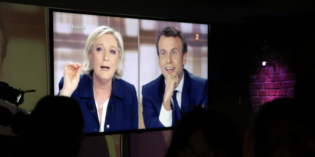 PARIS, FRANCE - MAY 03:  Supporters of President of the political movement 'En Marche !' ( Onwards !) and French presidential election candidate Emmanuel Macron watch the TV debate  between Emmanuel Macron and Marine Le Pen on a huge screen on May 03, 2017 in Paris, France. Macron and Le Pen arrived in the lead positions in the first round of the French presidential elections. France will hold the second round on May 07, 2017.  (Photo by Chesnot/Getty Images)