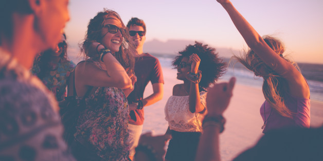 Group of friends dancing on the beach at a sunset beachparty on a summer evening