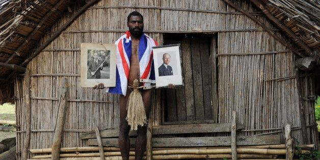 TO GO WITH AFP STORY 'Vanuatu-Britain-religion-royals,FEATURE' by Madeleine Coorey Sikor Natuan, the son of the local chief, holds two official portraits (one holding a pig-killing club, L) of Britain's Prince Philip in front of the chief's hut in the remote village of Yaohnanen on Tanna in Vanuatu on August 6, 2010. In his remote village in Vanuatu, tribesman Sikor Natuan cradles a faded portrait of Britain's Prince Philip against his naked and tattooed chest. Natuan, who just weeks before danced and feasted to mark the royal's 89th birthday, is already preparing for next year's celebrations -- and he is expecting the guest of honour to attend, despite his advanced age. For in the South Pacific village of Yaohnanen on Vanuatu's Tanna island, where men wear nothing but grass penis sheaths, and marijuana and tobacco grow wild, Prince Philip is worshipped as a god.  AFP PHOTO / Torsten BLACKWOOD (Photo credit should read TORSTEN BLACKWOOD/AFP/Getty Images)