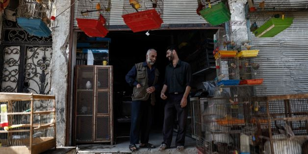 Syrian men chat in front of a shop selling animals in the rebel-held town of Douma, on the eastern outskirts of Damascus on May 6, 2017. Fighting subsided in Syria after a deal signed by government backers Russia and Iran and rebel supporter Turkey to create four safe zones began to take effect, a monitor said. / AFP PHOTO / Sameer Al-Doumy        (Photo credit should read SAMEER AL-DOUMY/AFP/Getty Images)
