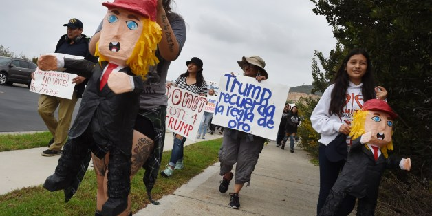 People carry Trump Pinatas during a protest rally denouncing alleged racist remarks by Republican presidential candidate Donald Trump, at the Trump National Golf Club in Palos Verdes, California on October 17, 2015.      AFP PHOTO / MARK RALSTON        (Photo credit should read MARK RALSTON/AFP/Getty Images)
