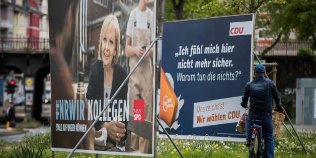 DUESSELDORF, GERMANY - MAY 03: A man rides a bicycle past election campaign billboards of the German Social Democrats (SPD) and the German Christian Democrats (CDU) ahead of state elections in North Rhine-Westphalia on May 3, 2017 in Duesseldorf, Germany. North Rhine-Westphalia is Germany's most populous state and will hold state elections on May 14. According to a recent poll the German Christian Democrats (CDU) and the German Social Democrats (SPD) are in a tight race for the lead while the po