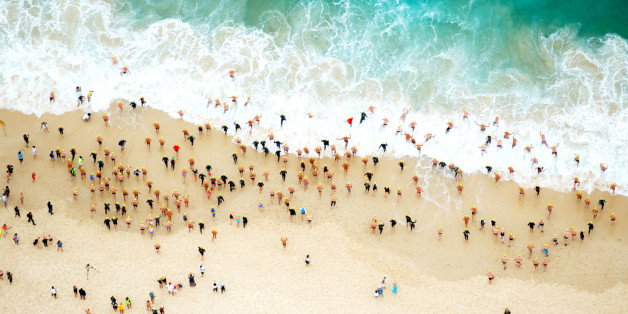 An aerial image of a group of swimming running in the the ocean at the start of a race.