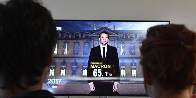 A couple watch a TV screen displaying French President elected Emmanuel Macron with an estimated score of more than 65 precent, on May 7, 2017 in Hede-Bazouges, western France. Pro-European centrist Emmanuel Macron won France's landmark presidential election, first estimates showed today, heading off a fierce challenge from the far-right in a pivotal vote for the future of the divided country and Europe. / AFP PHOTO / DAMIEN MEYER        (Photo credit should read DAMIEN MEYER/AFP/Getty Images)