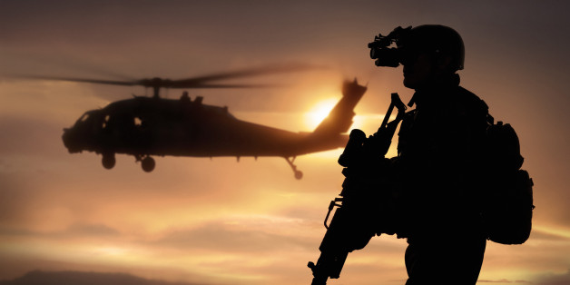 Combat ready special operation forces soldier in an Afghanistan war scene with a black hawk helicopter.