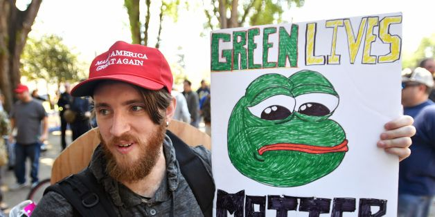 Andrew Knight holds a sign of Pepe the frog, a conservative icon, during a rally in Berkeley, California on April 27, 2017. 