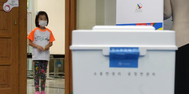 제19대 대통령 선거일인 9일 경기 고양시 신원초등학교에 마련된 투표소에서 한 어린이가 투표함을 바라보고 있다.