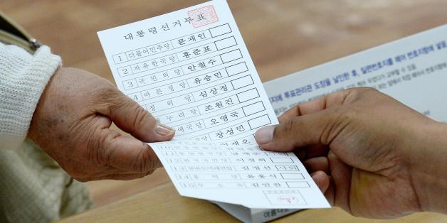 제19대 대통령선거일인 9일 오전 서울 송파문화원에 마련된 잠실7동 제1투표소에서 한 유권자가 투표를 하기위해 투표용지를 받고 있다.