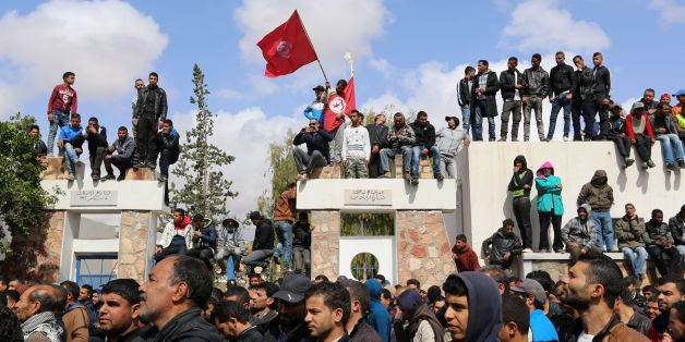 Tunisians wave their national flag as they take part in a general strike against marginalization and to demand development and employment on April 11, 2017, in Tataouine, south of Tunisia. / AFP PHOTO / FATHI NASRI        (Photo credit should read FATHI NASRI/AFP/Getty Images)