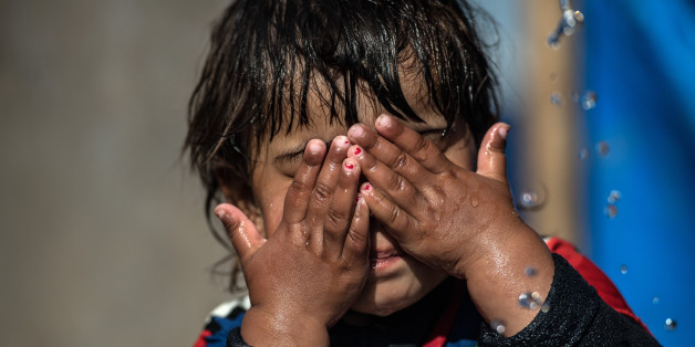 MOSUL, IRAQ - APRIL 15: A little girl washes her face under a tap in Khazir refugee camp on April 15, 2017 near Mosul, Iraq. Khazir camp, with a capacity of roughly 30,000 and along with several other camps near the city of Mosul, provides home for the approximately 300,000 people who have fled Iraq's second largest city as Iraqi government forces continue the military campaign to recapture the city from Islamic State who captured it in 2014.  (Photo by Carl Court/Getty Images)