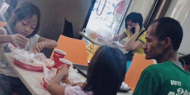"""Der """"selbstlose Vater"""" sieht seinen Kindern beim Essen zu. Für drei Mahlzeiten hat das Geld nicht gereicht."""