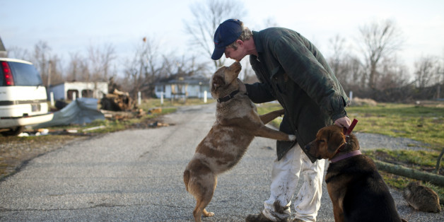 Mike Franke reunites with his dog in Marysville, Indiana March 3, 2012. The latest in a series of powerful tornadoes raked across a broad swath of the U.S. Midwest and Southeast, killing at least 33 people in four states, authorities said on Saturday. The fast-moving twisters on Friday splintered homes, damaged a prison and tossed around vehicles across the region, leaving 14 dead in Indiana, officials said. REUTERS/Aaron Bernstein (United States - Tags: ENVIRONMENT DISASTER)