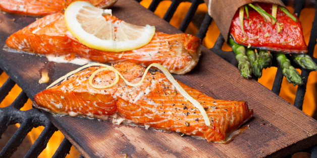 Three wild-caught salmon filets on a cedar plank in a backyard grill.  Fist is bright reddish orange and is topped with lemon, dill and cracked pepper file_thumbview_approve.php?size=1&id=19631280