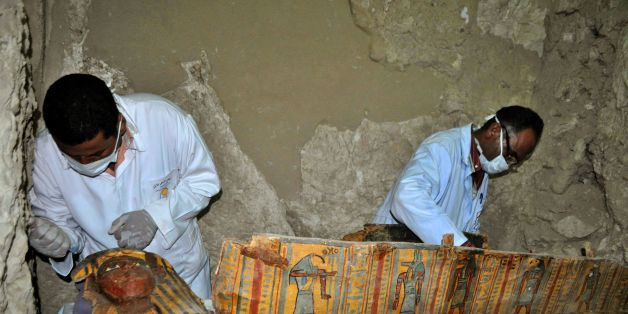 Members of an Egyptian archaeological team work on a wooden coffin discovered in a 3,500-year-old tomb in the Draa Abul Nagaa necropolis, near the southern Egyptian city of Luxor, on April 18, 2017.Egyptian archaeologists have unearthed several mummies, colourful wooden coffins and more than 1,000 funerary statues in the 3,500-year-old tomb, the antiquities ministry said. / AFP PHOTO / STRINGER        (Photo credit should read STRINGER/AFP/Getty Images)