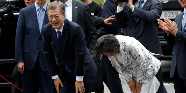 South Korea President Moon Jae-in and his wife Kim Jung-sook bow to greet to neighborhood residents as they arrive at the presidential Blue House in Seoul, South Korea May 10, 2017. REUTERS/Kim Kyung-Hoon