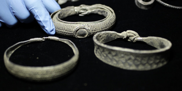 A museum assistant holds a Viking arm-ring at the British Museum in London December 14, 2011. The coins form part of the Silverdale Viking Hoard, which contains a total of 201 silver objects and a well preserved lead container, and was discovered in September 2011 with a  metal-detector in the Silverdale area of North Lancashire.     REUTERS/Stefan Wermuth (BRITAIN - Tags: ENTERTAINMENT SOCIETY)