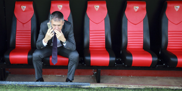 Levante's coach Lucas Alcaraz sits on the bench as he speaks on the mobile phone at the end of their Spanish First Division soccer match against Sevilla at Ramon Sanchez Pizjuan stadium in Seville, November 9, 2014. REUTERS/Marcelo del Pozo (SPAIN - Tags: SPORT SOCCER)