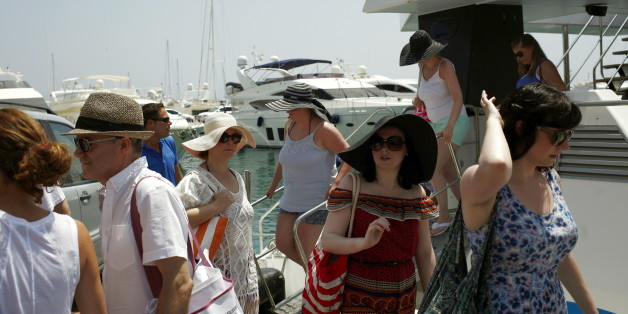 Tourists disembark a sightseeing boat at Puerto Banus in Marbella, on Costa del Sol, southern Spain, July 12, 2015. The Spanish government raised the terror-alert level to 4, out of a maximum of 5, after the attacks in France, Tunisia and Kuwait, Spain's Interior Minister Jorge Fernandez Diaz announced on June 26. Picture taken July 12, 2015. REUTERS/Jon Nazca