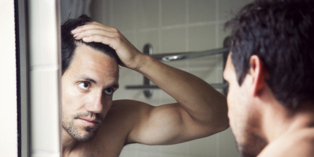 Man checking hair in mirror.