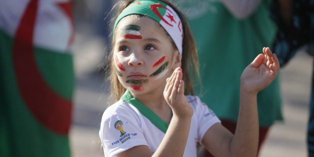 ALGIERS, ALGERIA - JUNE 17: Fans of Algeria watch their national team's soccer match with Belgium during the 2014 FIFA World Cup Group H, on the giant screens at the Al Barid square in different costumes on June 17, 2014 in Algiers, Algeria. A little girl with her painted face is seen at the square. (Photo by Bechir Ramzy/Anadolu Agency/Getty Images)