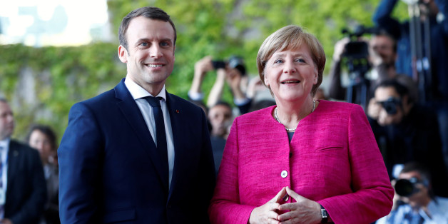 German Chancellor Angela Merkel and French President Emmanuel Macron arrive at a ceremony at the Chancellery in Berlin, Germany, May 15, 2017.    REUTERS/Fabrizio Bensch