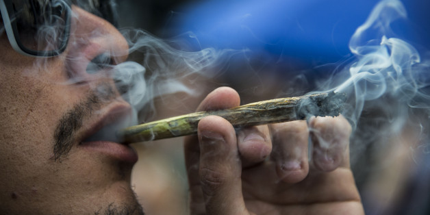 A demonstrator smokes a joint during a march calling for the legalization of marijuana along Paulista Avenue in Sao Paulo, Brazil, on May 6, 2017. / AFP PHOTO / NELSON ALMEIDA        (Photo credit should read NELSON ALMEIDA/AFP/Getty Images)