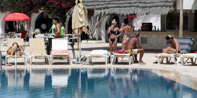 European tourists sunbathe at a hotel in the southern Mediterranean Tunisian resort island of Djerba, on May 13, 2017. / AFP PHOTO / FETHI BELAID        (Photo credit should read FETHI BELAID/AFP/Getty Images)