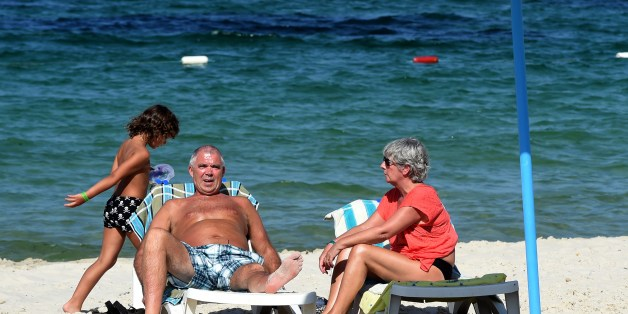 British tourists sit in the sun on July 10, 2015 in the Mouradi Hotel in the touristic Port el Kantaoui, on the outskirts of Sousse south of the capital Tunis. Denmark followed Britain's example in urging its nationals to cut short their holidays in Tunisia after London warned the country was still unsafe after last month's beach massacre. AFP PHOTO / FETHI BELAID        (Photo credit should read FETHI BELAID/AFP/Getty Images)
