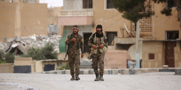 Members of the Syrian Democratic Forces (SDF), walk in the town of Tabqa, about 55 kilometres (35 miles) west of Raqa city, on May 18, 2017.On November 5, 2016, a US-backed alliance of Kurdish and Arab fighters began an operation to capture IS' de facto Syrian capital. On May 10, 2017, the SDF captured the city of Tabqa and an adjacent dam, the last big town before Raqa. / AFP PHOTO / DELIL SOULEIMAN        (Photo credit should read DELIL SOULEIMAN/AFP/Getty Images)