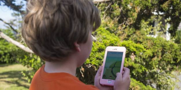 An unidentified boy searches his handset during a search with the Pokémon Go application in East Orleans, Massachusetts on July 10, 2016. (Photo by Robert Nickelsberg/Getty Images)