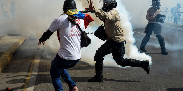 A riot policeman struggles with a demonstrator during a protest against the government of President Nicolas Maduro in Caracas on May 20, 2017.  Venezuelan protesters and supporters of embattled President Nicolas Maduro take to the streets Saturday as a deadly political crisis plays out in a divided country on the verge of paralysis. / AFP PHOTO / FEDERICO PARRA        (Photo credit should read FEDERICO PARRA/AFP/Getty Images)