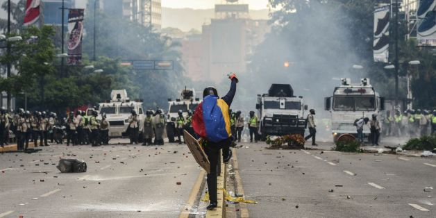 Riot police clash with demonstrators during a protest against the government of President Nicolas Maduro in Caracas on May 20, 2017. Venezuelan protesters and supporters of embattled President Nicolas Maduro take to the streets Saturday as a deadly political crisis plays out in a divided country on the verge of paralysis. / AFP PHOTO / FEDERICO PARRA        (Photo credit should read FEDERICO PARRA/AFP/Getty Images)